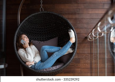 Beautiful happy girl dressed in white sweater and blue jeans lying in a bubble chair and talking  on the cellphone