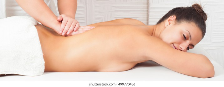 Beautiful happy girl enjoying massage therapy in professional health spa.