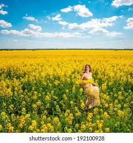 Beautiful happy girl having fun on the colza field. Healthy young woman outdoors. Countryside. General plan