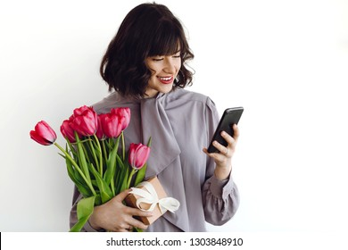 Beautiful happy girl holding red tulips, gift box and phone on white background indoors, space for text. Stylish young woman holding phone and flowers.  International womens day. Hello spring