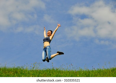 Beautiful and happy girl jumps high on grass