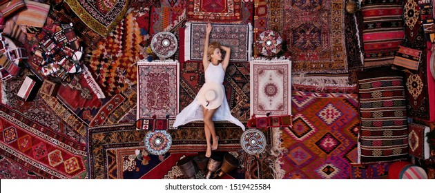 Beautiful happy girl in a long white dress laying on the carpet and rugs in Goreme, Cappadocia, Turkey. Top view drone.