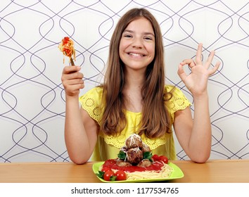 beautiful happy girl with meatballs and spaghetti and ok hand sign