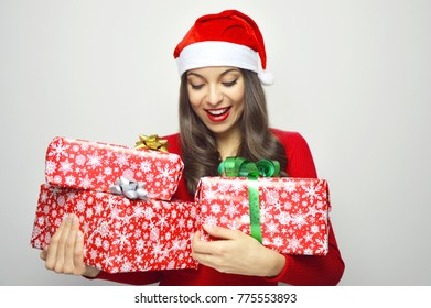 Beautiful happy girl with Santa Claus hat looks her christmas gifts on gray background
