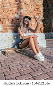 Beautiful happy girl sitting skateboard, longboard. He holding smartphone his hand, talking video call online application Internet. Taking pictures yourself makes selfie. In summer city has rest.