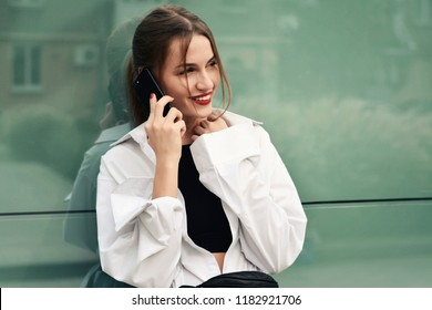 Beautiful happy girl with smartphone on the street