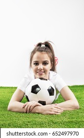 Beautiful happy girl in a sports T-shirt with a soccer ball lies on the green grass. Gray background.