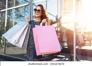 Beautiful happy girl in sunglasses, with bags in her hands, shopping in the city.