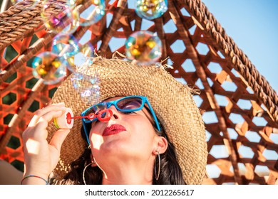 beautiful happy girl with sunglasses making soap bubbles outdoor