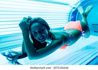 beautiful happy girl in swimsuit sunbathing in horizontal sunbed under ultraviolet rays, smiling