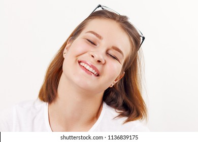 Beautiful happy girl teenager with glasses smiles with closed eyes in white studio