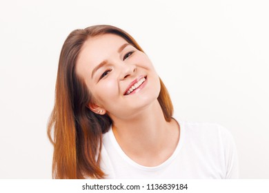 Beautiful happy girl teenager in t-shirt smiles in white studio