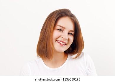 Beautiful happy girl teenager in white t-shirt smiles in white studio