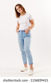 Beautiful happy girl teenager in white t-shirt and jeans poses in white studio
