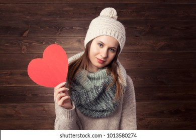 Beautiful happy girl with Valentine Gift heart. Smiling surprised model girl in winter cloths. Wooden background.
