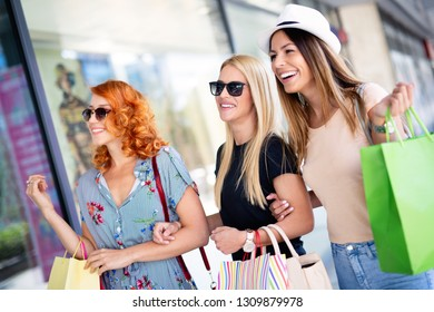 Beautiful happy girls holding shopping bags and smiling outdoors