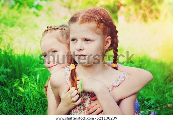 Beautiful Happy Girls with Red Hair outdoors in Summer. Healthy Children. Family Concept - Sisters Love