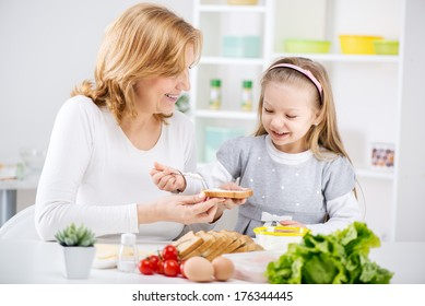 Beautiful happy grandmother and her cute granddaughter making Sandwich in the kitchen.