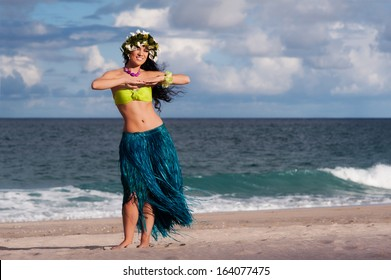 A beautiful, happy hula dancer poses on the beach.