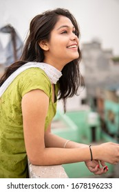 Beautiful happy Indian late teen girl enjoying fresh air in outdoor at day time. She is looking up and thinking with smile on her face. She is wearing traditional dress salwar Kameez and Dupatta.