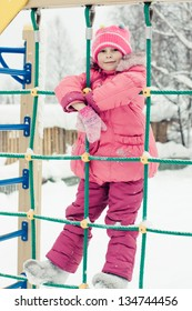 Beautiful happy kid in the red jacket in the winter outdoors.