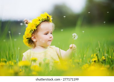 Beautiful happy little baby girl with a wreath on a meadow between yellow flowers dandelions