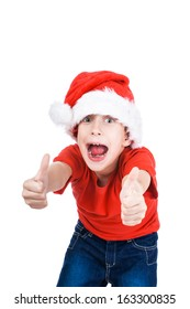Beautiful happy little boy wearing Santa's cap shows thumbs up screaming in excitement