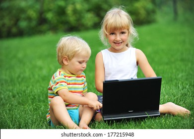 beautiful and happy little girl with brother sitting on grass with laptop computer