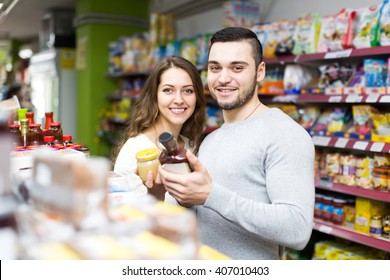 Beautiful and happy lovers buying convenience food in a local shop