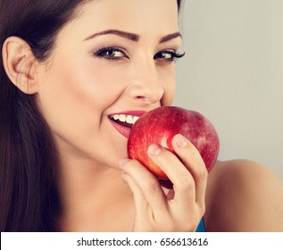 Beautiful happy makeup woman holding red tasty apple and biting it. Closeup portrait. Vintage toned