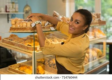 Beautiful happy mature African female baker working at her store decorating showcase smiling joyfully to the camera copyspace small business owner ownership occupation career service food industry