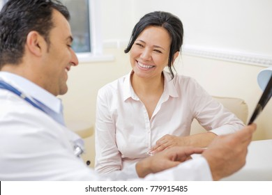 Beautiful happy mature Asian woman smiling joyfully while talking to her doctor during medical appointment at the local clinic. Therapist examining MRI or x-ray scan while talking to his patient