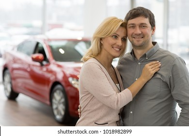 Beautiful happy mature couple embracing smiling to the camera posing at the dealership showroom after buying a new car copyspace automobile driving people lifestyle family marriage anniversary.