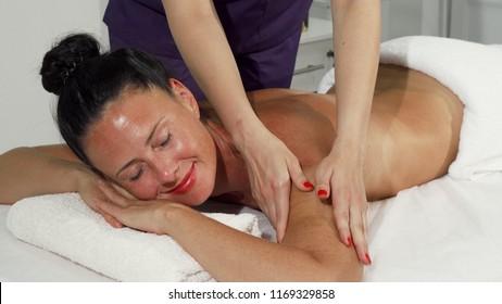Beautiful happy mature woman smiling while enjoying back massage