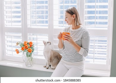 Beautiful happy middle age woman sitting on windowsill at home and looking at cat. Young woman with short hair drinking tea from mug and playing with pet. Relax, leisure time at home.