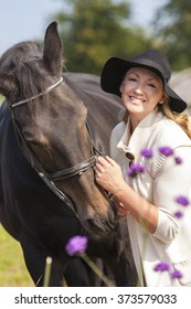 Beautiful happy middle aged woman wearing black floppy hat, smiling and stroking her horse in sunshine