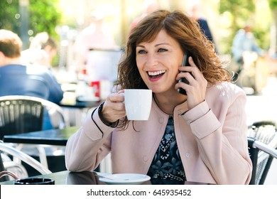 Beautiful and happy middle aged woman having coffee while talking on mobile phone