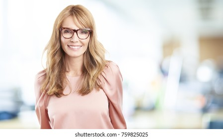 A beautiful happy middle aged woman standing inside and looking at you.