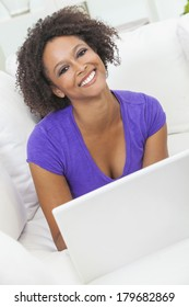 A beautiful happy mixed race African American girl or young woman laying down on sofa using a laptop computer