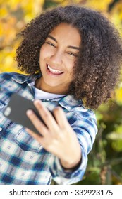 Beautiful happy mixed race African American girl teenager female child young woman smiling with perfect teeth taking selfie photograph with cell phone