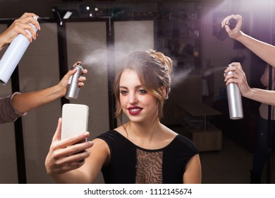 beautiful happy model with perfect makeup and coiffure is having fixation with hair sprays. four hands holding and pulverizing bottles. girl is taking a photo of herself