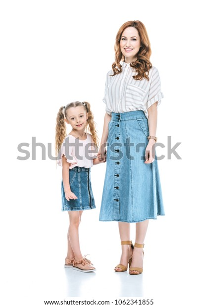 beautiful happy mother and daughter holding hands and smiling at camera isolated on white