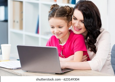 Beautiful happy mother and daughter using laptop at workplace