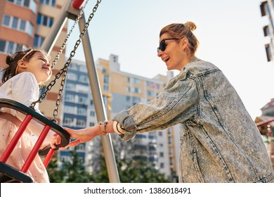 Beautiful happy mother and her kid are having fun outside. Mom is playing with her little daughter on a swing outdoor. Motherhood and childhood