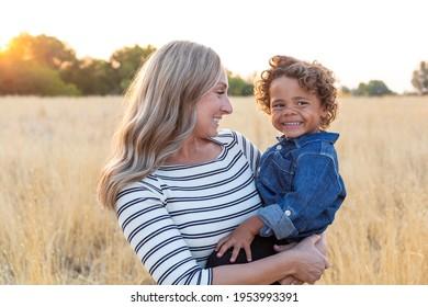 Schöne glückliche Mutter, die ihren bezaubernden, vielfältigen Sohn im Außenlicht hält. Sonnenstrahlen, die durch scheinen, während die Mutter ihrem Sohn Liebe und Zuneigung zeigt