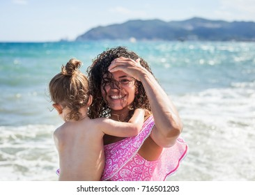 Beautiful and happy mother holding her little girl at the beach