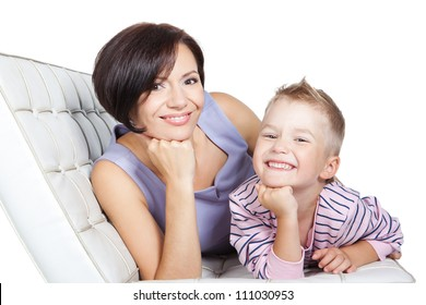 Beautiful happy mother and little son relaxing together on a sofa