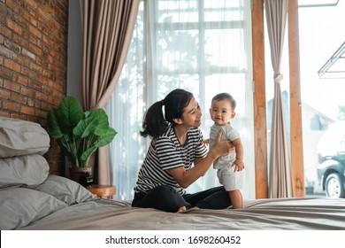 ベッドで赤ちゃんと遊んでいる美しい幸せな母親