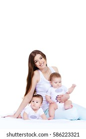 Beautiful happy mother playing with her baby children. Family concept. Healthy children. Isolated over white.