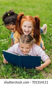 beautiful happy multiethnic girls reading book while lying together on grass